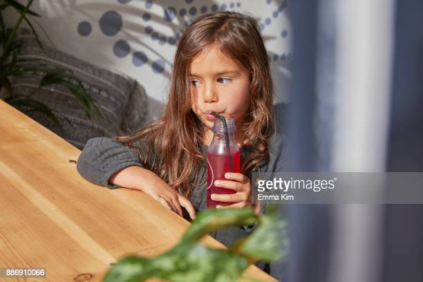 Young girl sitting at table, drinking juice from bottle using straw
