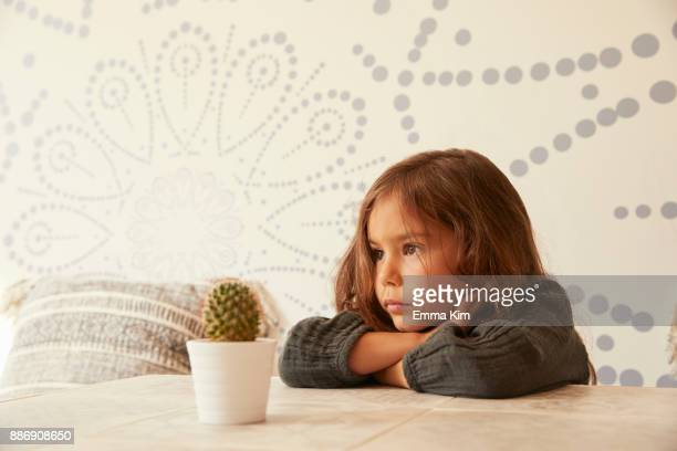 Young girl sitting at table, resting head on arms, pensive expression