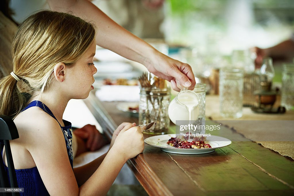 Young girl sitting at table waiting for dessert : Stock Photo