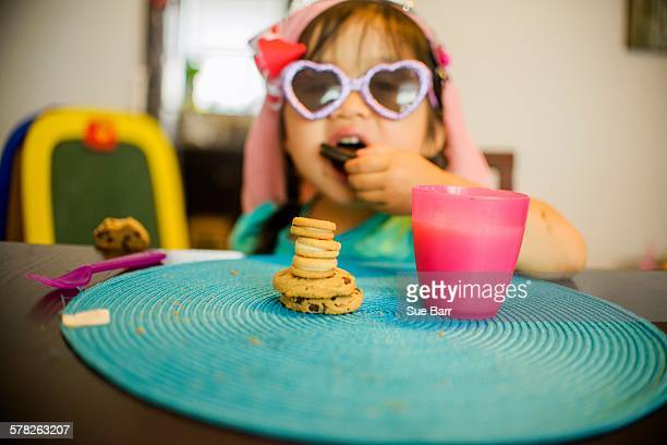 Young girl sitting at table with drink and cookies
