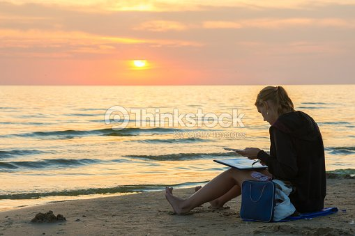 young girl sitting beach and draw sheet of watercolor sunset stock