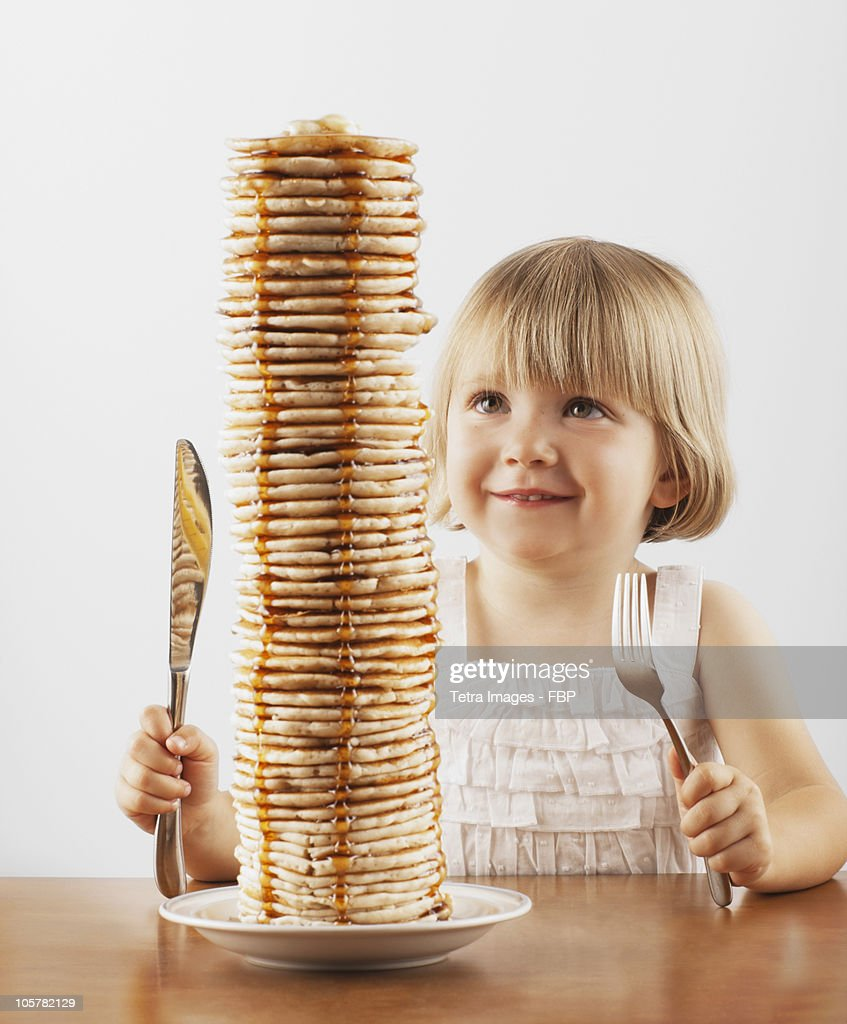 Young girl sitting behind a tall stack of pancakes : Stock Photo