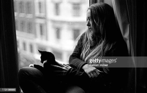 Young girl sitting by window with cat on lap