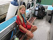 A young girl sitting in a boat with scuba gear, Moorea, Tahiti, French Polynesia, South Pacific