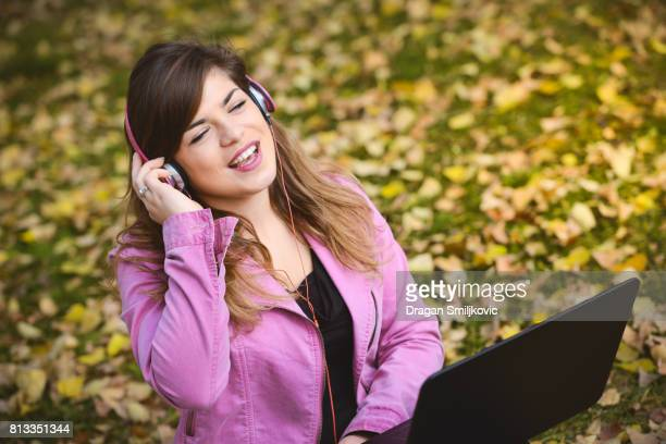 Young girl sitting in a park and listening music
