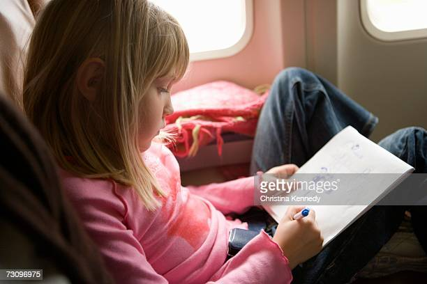 Young girl sitting in an airplane and drawing in a sketch pad