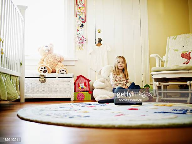 Young girl sitting in bedroom smiling