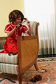 Young girl (8-9 years) sitting in chair cutting bangs with scissors
