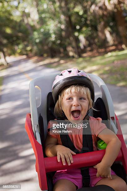 Young girl sitting in childs bicycle seat, enjoying journey