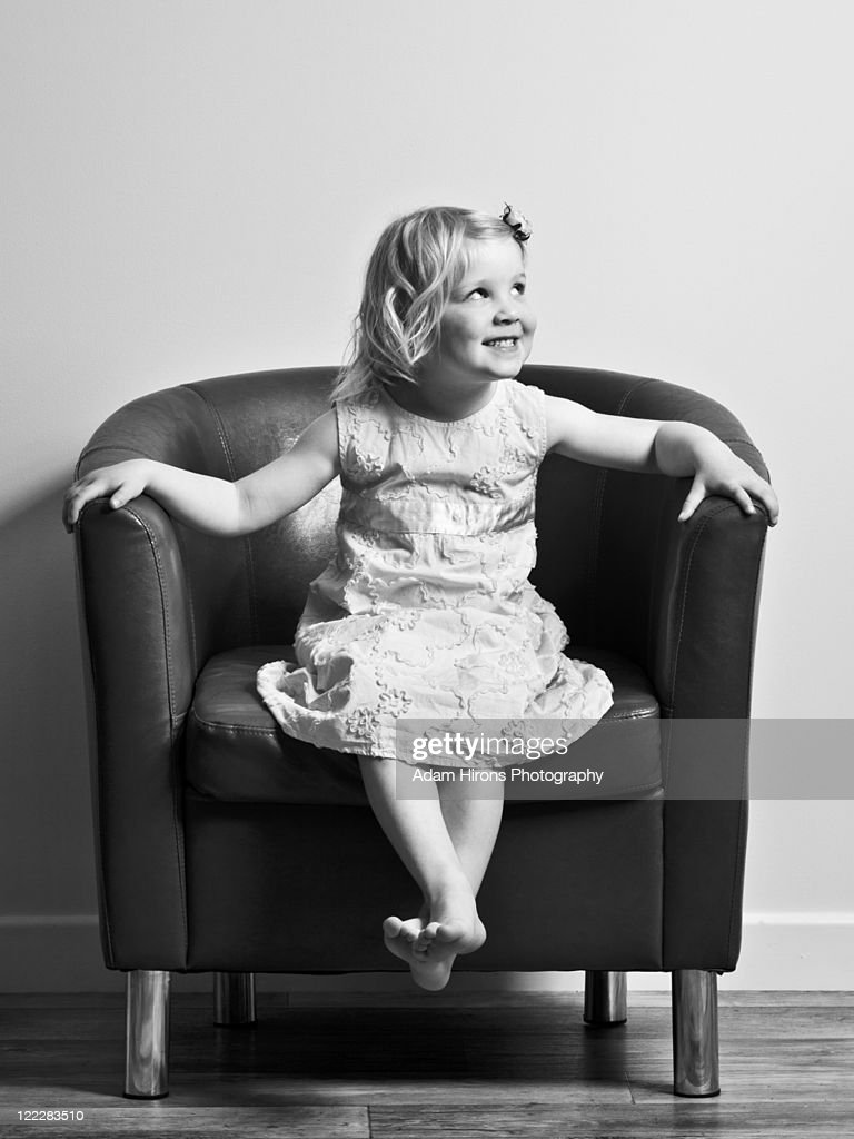 Black child sitting in chair - Young Girl Sitting In Large Chair Looking Right Stock Photo