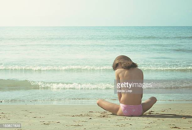 Young girl sitting on a beach at dawn