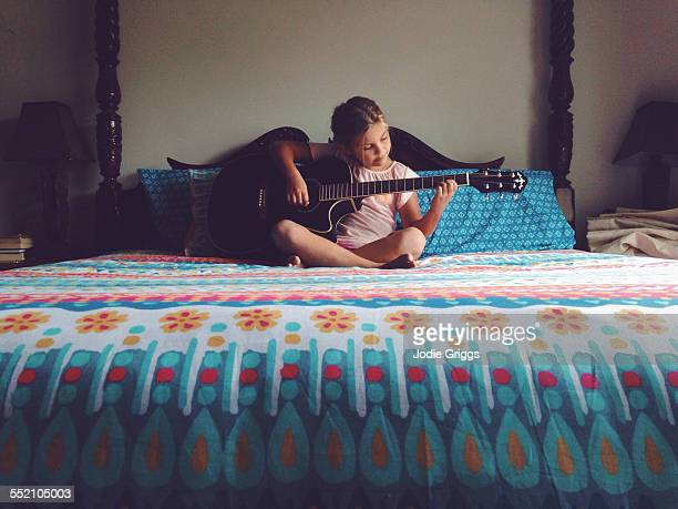 Young girl sitting on a bed playing the guitar