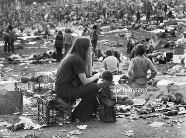 A young girl sitting on a milk crate watches the dawn break amid a crowd in a meadow filled with mud and debris at the Aquarian music festival in...