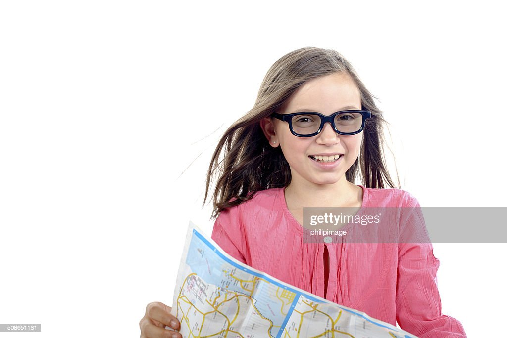 young girl sitting on a suitcase looking at a map : Stock Photo
