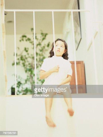 Young girl sitting on balcony, thinking : Stock Photo