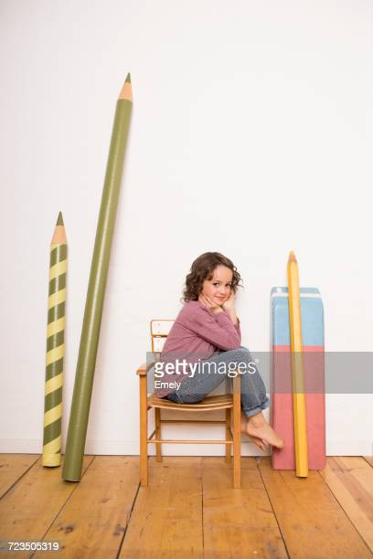 Young girl sitting on chair, giant size stationary leaning on wall beside her
