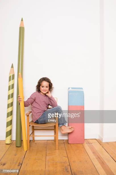 Young girl sitting on chair, holding giant size pencil, giant size stationery leaning on wall beside her