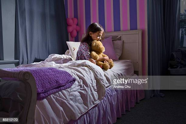Young girl sitting on her bed in deep thought.