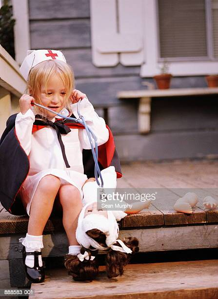 Young girl (4-6) sitting on porch, playing nurse with doll