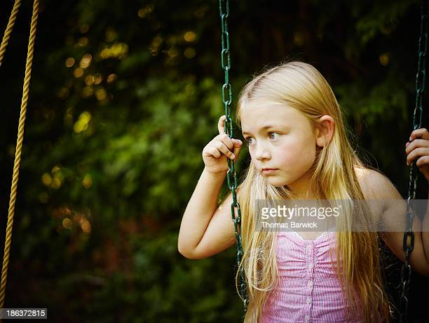 Young girl sitting on swing looking out