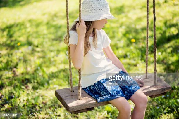 Young girl sitting on swing