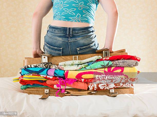 Young girl sitting on top of overflowing suitcase