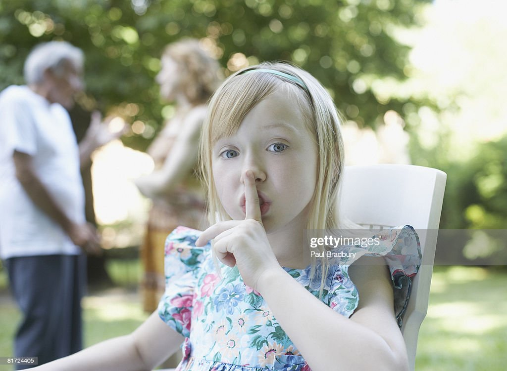 Young girl sitting outdoors with finger to lips shushing : Stockfoto