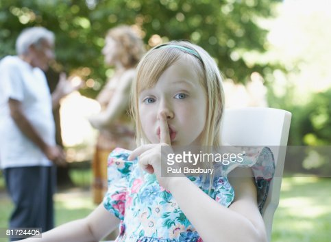 Young girl sitting outdoors with finger to lips shushing : Stock Photo