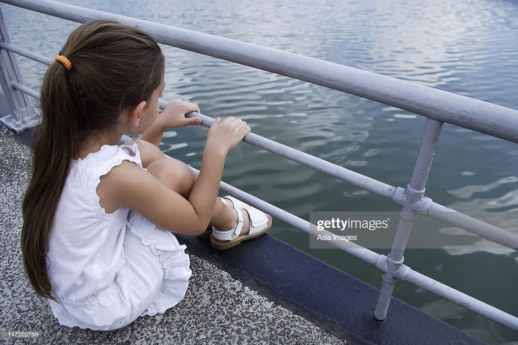 young girl sitting over lake : Stock Photo