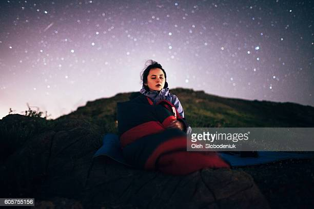 Young girl sitting under the starry sky