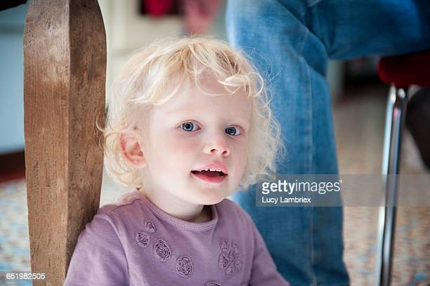 Young girl sitting under the table