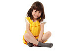 Cute little girl in a yellow dress sits on the floor and smiles for the camera. Horizontal shot. Isolated on white.