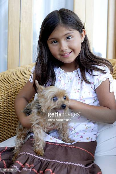 Young girl (6-7) sitting with small dog, portrait