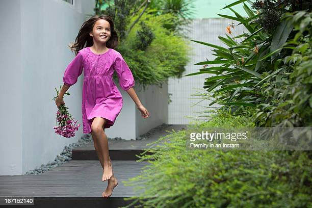Young girl skipping whilst holding flowers
