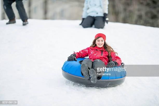 Junges Mädchen Schlittenfahren auf einem Hügel
