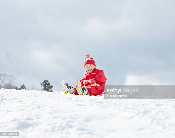 Young girl sledging downhill