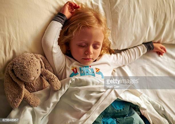 Young girl sleepign with stuffed rabbit