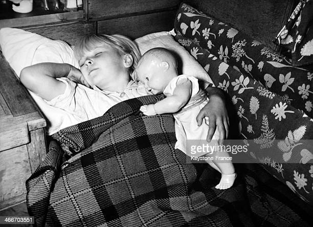 Young girl sleeping holding her doll Illustration circa 1960 in United Kingdom