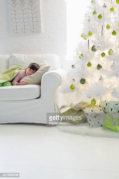 Young Girl Sleeping on a Sofa in a Living Room Next To an Artificial Christmas Tree