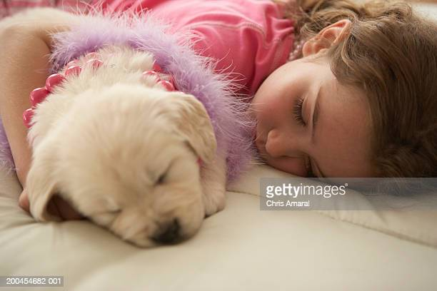 Young girl (8-10) sleeping on bed with dog