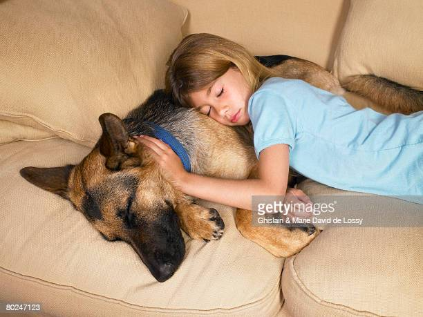 Young girl sleeping on her dog.