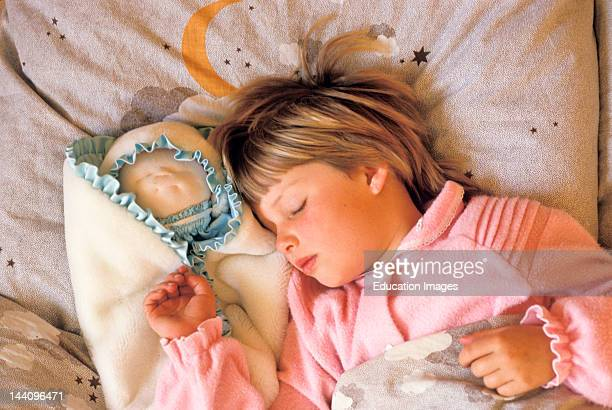 Young Girl Sleeping With Doll At Her Side