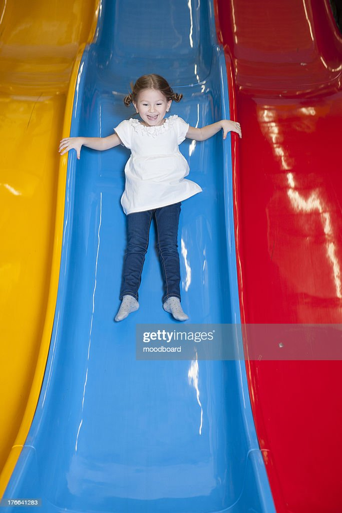Young girl slides down colorful slide