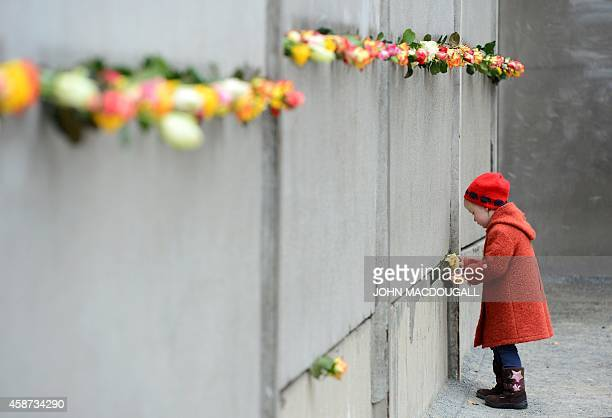 A young girl slips a rose in a preserved segment of the Berlin Wall during the commemorations to mark the 25th anniversary of the fall of the Berlin...