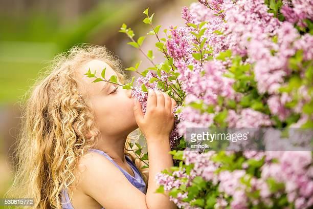 Junges Mädchen riechen Lila Blüten im Frühling