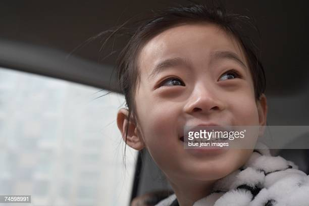 Young girl smiles in the back seat of a car