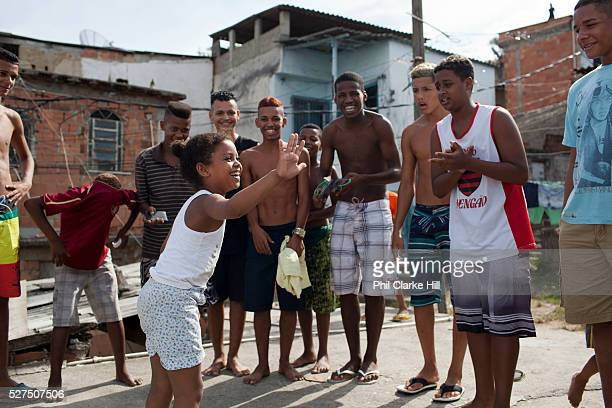 Young girl smiling and gesturing to a group of young men guys on a rooftop dancing passinho to funk Carioca Baile funk Vila Valquiere West Zone Zona...