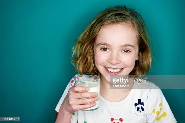 young girl smiling and holding glass of milk
