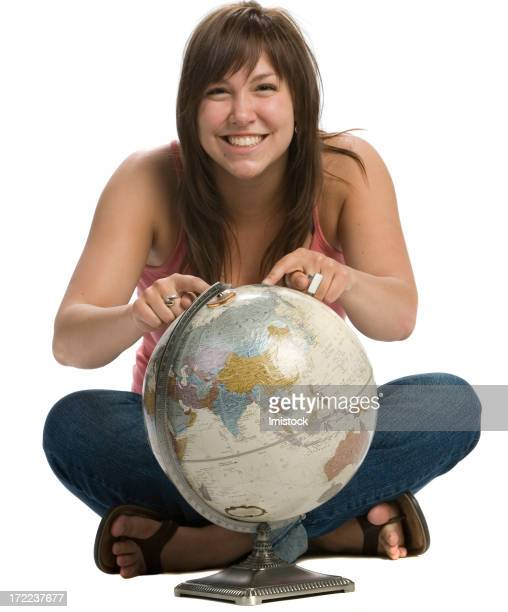 young girl smiling and pointing on an area of  globe