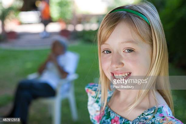 Young girl smiling outdoors with senior man in background